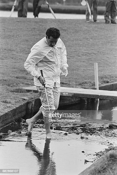 Scottish golfer Sam Torrance pictured bare footed as he paddles in a stream to look for his ball during play for Team Europe to win the 1985 Ryder...