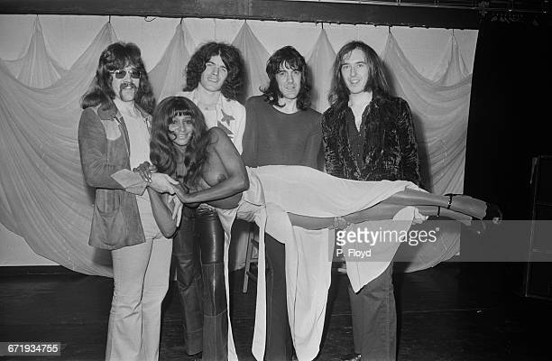 Scottish hard rock band Nazareth pose with a topless woman UK 27th October 1971 From left to right drummer Darrell Sweet singer Dan McCafferty lead...