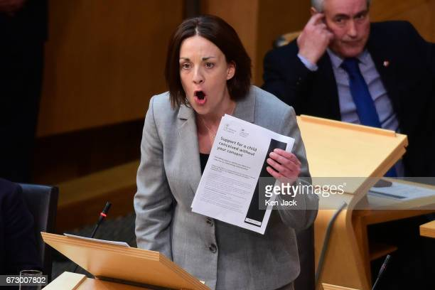Scottish Labour leader Kezia Dugdale holds up a copy of the form women are required to fill in to claim tax credits for a child conceived as a result...
