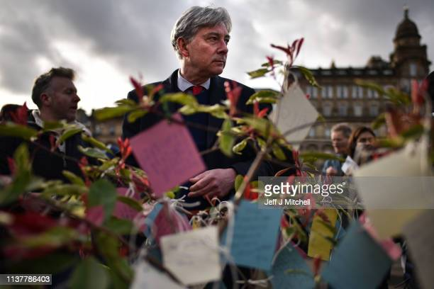 Scottish Labour Party leader Richard Leonard attaches a message to a tree as they attend a vigil in George Square to pay their respects to the...
