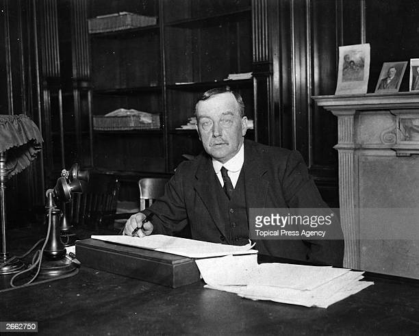 Scottish Labour politician Arthur Henderson sitting at his desk. Henderson was born in Glasgow but brought up in Newcastle where he worked as an iron...
