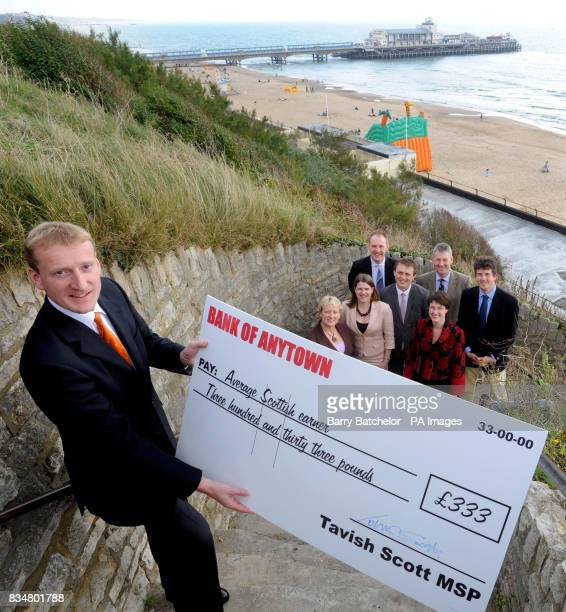 Scottish Liberal Democrat leader Tavish Scott holds a large cheque above the beach during the Lib Dem's party conference in Bournemouth PRESS...