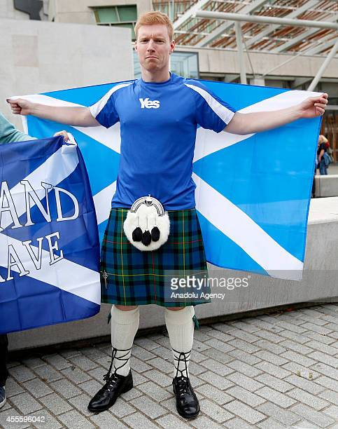Scottish man wearing kilt holds Scotland flag on the sidewalk ahead of referendum on Scotland's independence in Edinburgh, Scotland on September 17,...