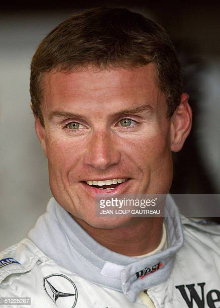 Scottish McLaren-Mercedes driver David Coulthard smiles as he chats with a techician in the pits of the Spa-Francorchamps racetrack during the first...