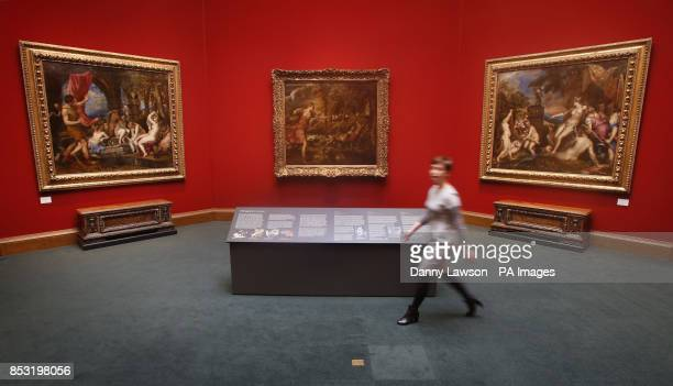 Scottish National Gallery employee Patricia Convery walks past three paintings by Titian Diana and Actaeon The Death of Actaeon and Diana and...