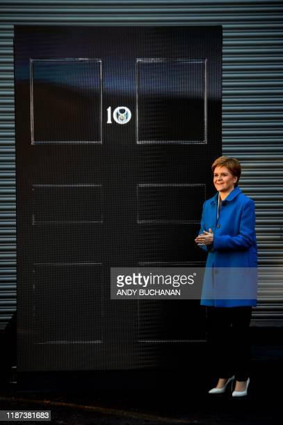 Scottish National Party leader and Scotland's First Minister Nicola Sturgeon poses with an LED display showing a representation of the door of 10...
