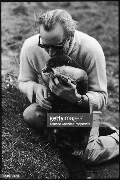 Scottish naturalist Gavin Maxwell plays with a pet otter outside his home, Sandaig, near Glenelg, Scotland, December 11, 1963.