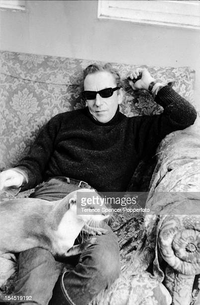 Scottish naturalist Gavin Maxwell sits on a sofa with a pet otter in his home, Sandaig, near Glenelg, Scotland, December 11, 1963.