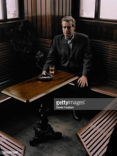 Scottish novelist William McIlvanney pictured seated at a table with a glass of whisky and a cigarette in a Glasgow pub.