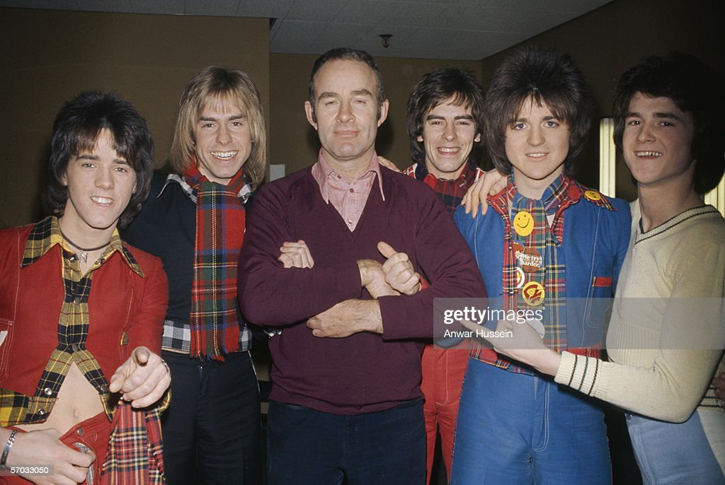 Scottish pop group the Bay City Rollers with their manager Tam Paton, circa 1975. Left to right: Stuart ('Woody') Wood, Derek Longmuir, Tam Paton, Alan Longmuir, Eric Faulkner and Les McKeown.