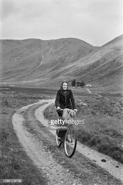 Scottish postwoman Jean Cameron cycles along a farm track after delivering letters to an isolated cottage in the Glen Clova valley near Dundee,...