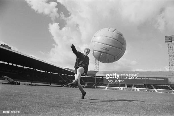 Scottish professional footballer and forward with Manchester United, Denis Law pictured in training on the pitch at the club's Old Trafford ground in...