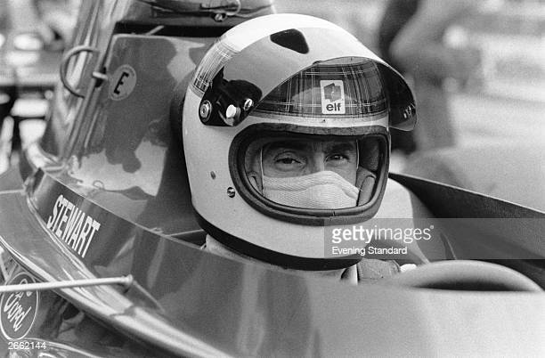 Scottish racing driver Jackie Stewart in his car before the British Grand Prix at Silverstone Stewart born in Dumbarton raced Formula 1 cars between...