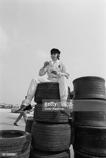 Scottish racing driver Jackie Stewart takes a tea break on top of a pile of tyres at Silverstone 10th July 1969 He has just set a new record for the...