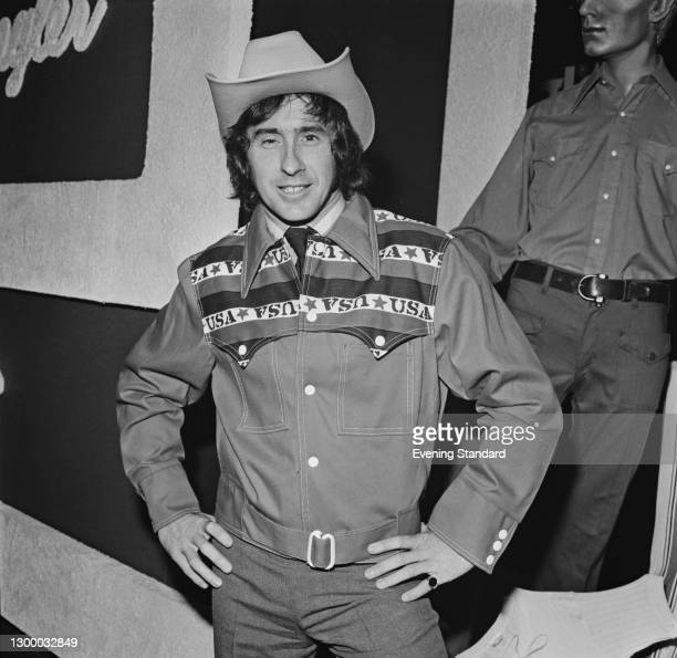 Scottish racing driver Jackie Stewart wearing a 'USA' jacket and a cowboy hat during an advertising deal with Wrangler, UK, 24th February 1972.