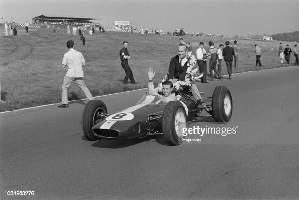 Scottish racing driver Jim Cark pictured driving his Team Lotus Lotus 25 Climax V8 Italian Grand Prix winning car, with team owner Colin Chapman...