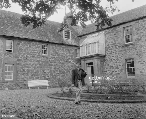 Scottish racing driver Jim Clark heads out with his shotgun at the family home Edington Mains Farm in Berwickshire UK August 1963