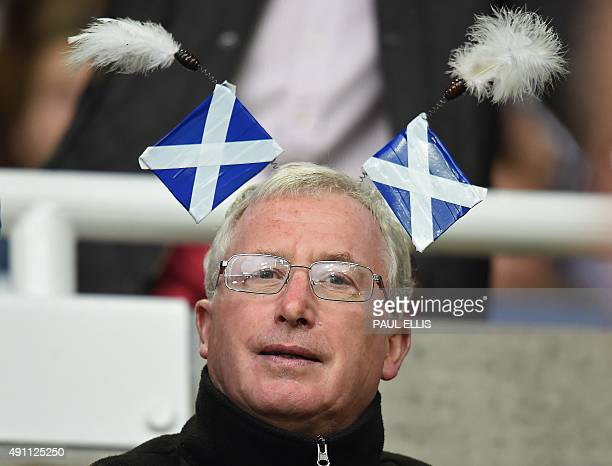 A Scottish rugby fan sits in wears Saltire flags on his head as he awaits the start of a Pool B match of the 2015 Rugby World Cup between South...