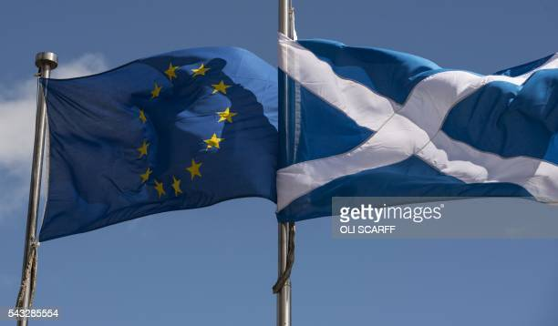 A Scottish Saltire and a European Union flag fly in front of the Scottish Parliament building in Edinburgh Scotland on June 27 2016 British leaders...