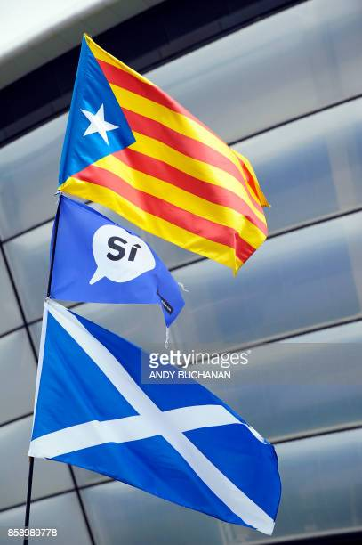 A Scottish Saltire flag and the Catalan proindependence 'Estelada' flag flying outside the venue on the opening day of the Scottish National Party...