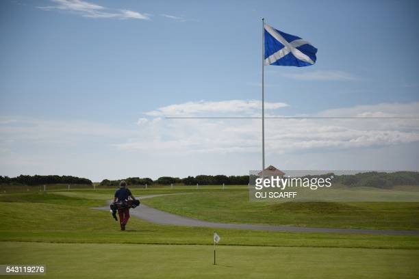 A Scottish Saltire flag flies from a pole as a golfer walks between holes at the newlyrenovated Trump Turnberry hotel and golf resort in Turnberry...