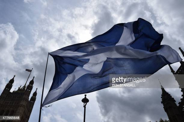 A Scottish Saltire flag flies outside the Houses of Parliament during a photocall of newlyelected Scottish National Party members of parliament in...