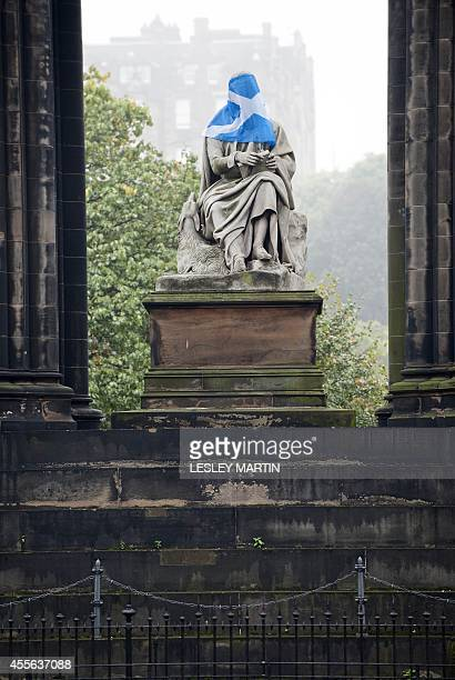 A Scottish Saltire flag is placed across the face of a statue of Scottish novelist and playwright Sir Walter Scott in Edinburgh Scotland on September...