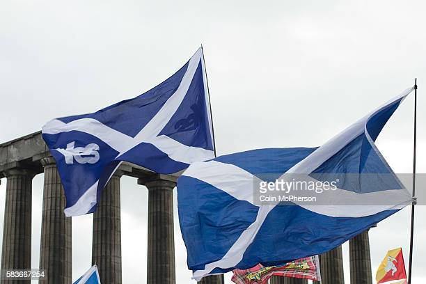 A Scottish saltire flag with the word 'Yes' is waved by crowds listening to speeches on Calton Hill in Edinburgh during a proIndependence march and...