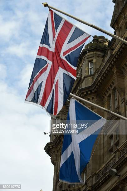A Scottish Saltire flies alongside a between a Union flag outside the Balmoral Hotel in Edinburgh on March 13 2017 Scotland's announcement on Monday...