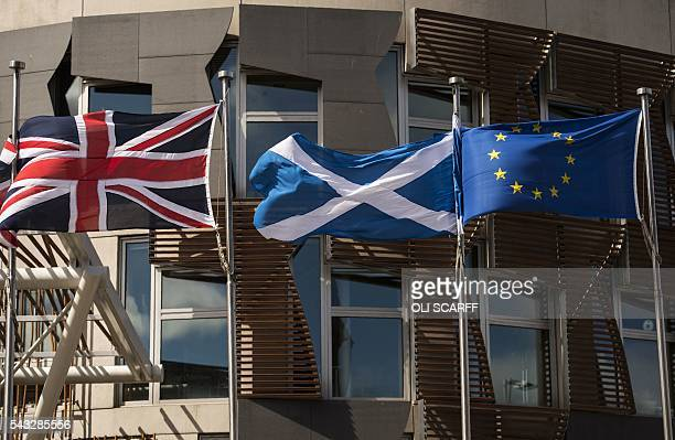 A Scottish Saltire flies between a Union flag and a European Union flag in front of the Scottish Parliament building in Edinburgh Scotland on June 27...
