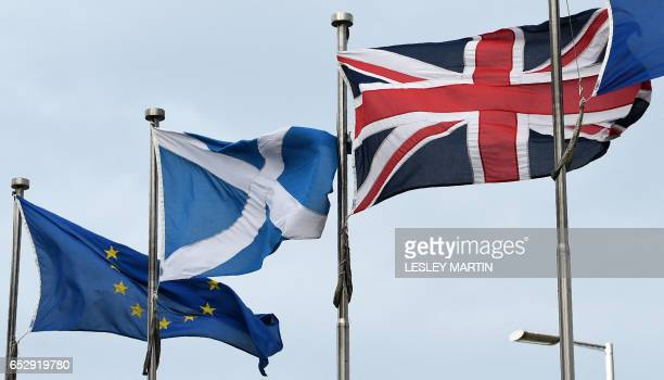 A Scottish Saltire flies between a Union flag and a European Union flag in front of the Scottish Parliament building in Edinburgh on March 3 2017...