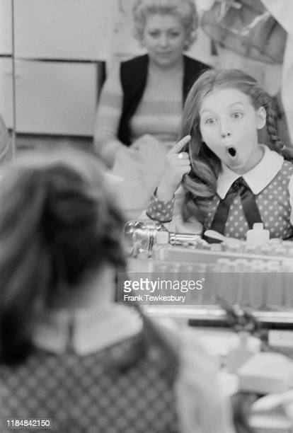 Scottish singer and a television show host Lena Zavaroni makes a surprised expression while looking at herself in a mirror backstage, UK, 20th...