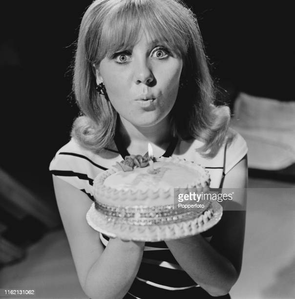 Scottish singer Lulu pictured holding a birthday cake during filming of an episode of The Des O'Connor Show for Associated Television in October 1965