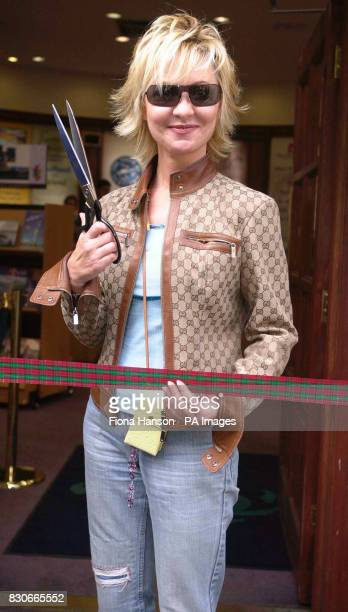 Scottish singer Lulu prepares to cut a tartan ribbon at the Scottish Tourist Board in central London to open the Great Scotland Sale of cutprice...