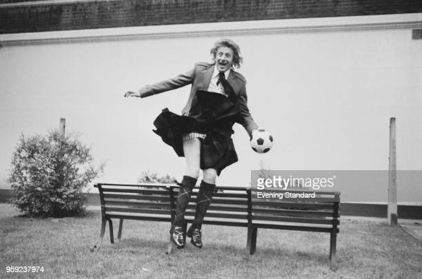 Scottish soccer player Denis Law jumping over a bench while wearing a traditional Scottish kilt and holding a soccer ball UK 24th May 1978