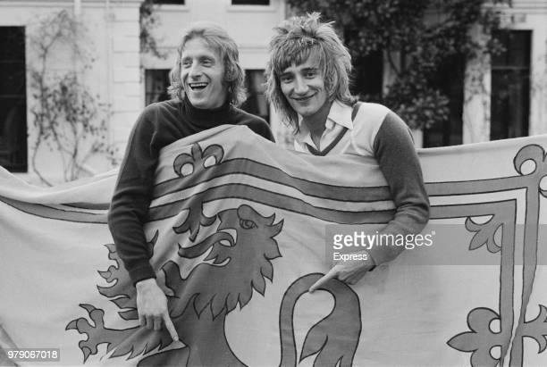 Scottish soccer player Denis Law of Manchester City FC with British singersongwriter Rod Stewart both are holding a Royal Banner of Scotland UK 18th...