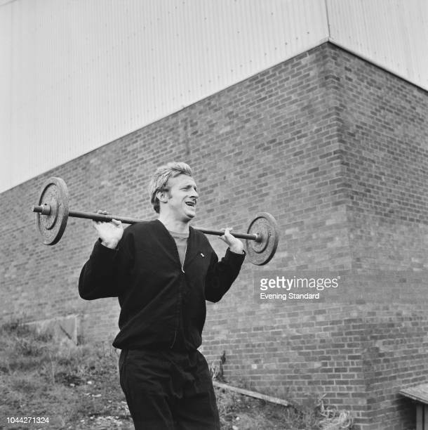 Scottish soccer player Denis Law of Manchester United FC training outdoors with a barbell UK 1st August 1968