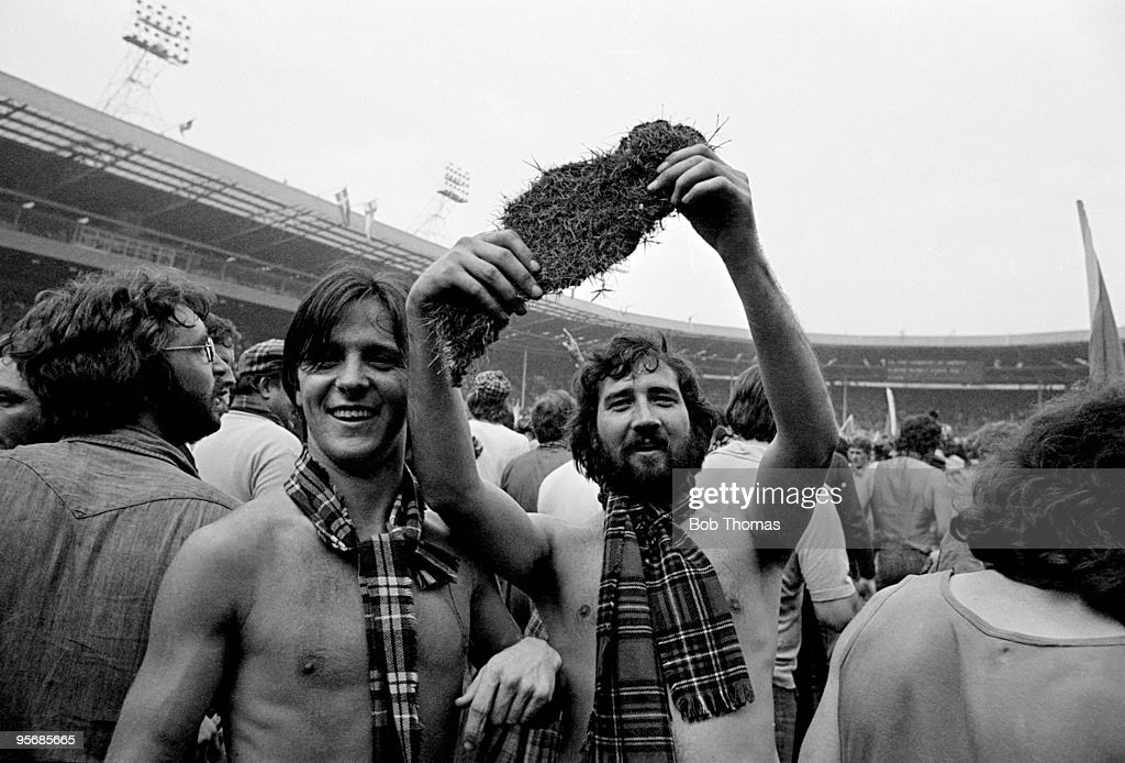Scottish supporters take home a piece of the Wembley turf after invading the pitch at the end of the British Home Championship match between England and Scotland at Wembley Stadium in London, 4th June 1977. Scotland won 2-1.
