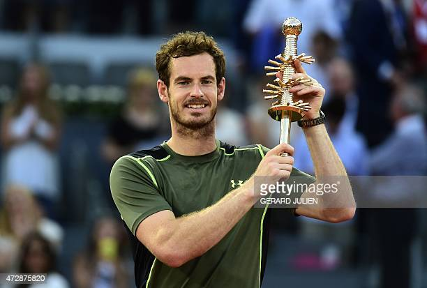 Scottish tennis player Andy Murray poses with his trophy as he celebrates his victory over Spanish tennis player Rafael Nadal at the end of the men...