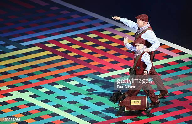 Scottish Terrier walks with his handler as the team name bearer for Scotland during the Opening Ceremony for the Glasgow 2014 Commonwealth Games at...
