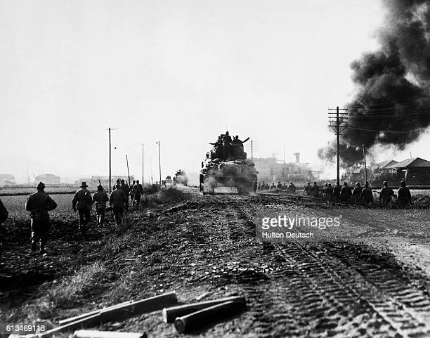 Scottish Troops Enter Burning Chonju. While tanks trundle along the primitive roads, men of the Argyll and Sutherland Highlanders, advance along the...