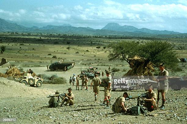 Scottish troops go through fire drills with their water cooled Vickers machine guns at their base in Aden A Ferret armoured car is parked in the...