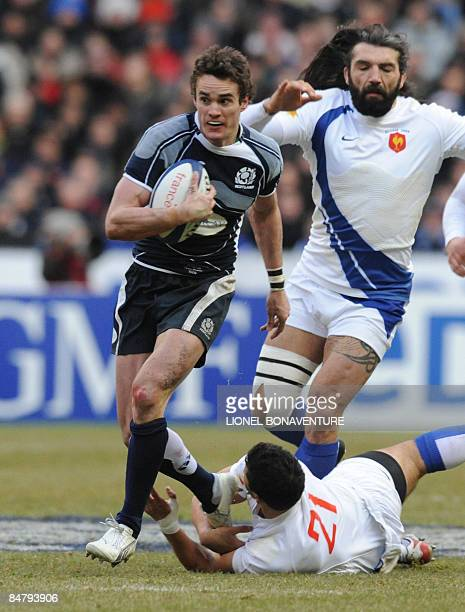 Scottish wing Thom Evans tries to escape from French lock Sebastien Chabal and French center Maxime Mermoz during their six Nations rugby union match...