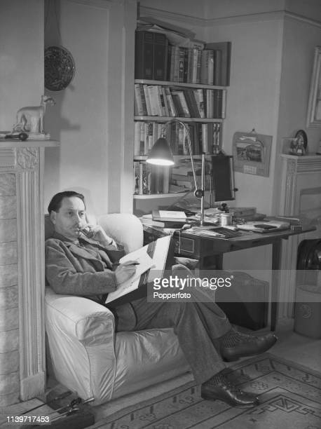 Scottish writer and author Sir Compton Mackenzie pictured smoking a pipe whilst writing in a study at home in Hampstead, London on 16th February 1939.