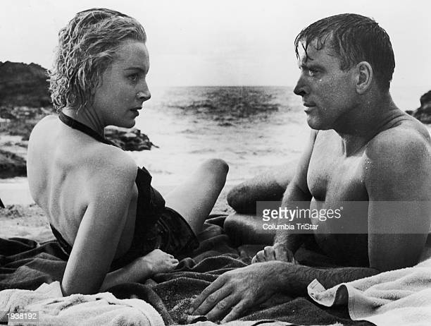 Scottishborn actor Deborah Kerr and American actor Burt Lancaster lay on the beach in a still from the film 'From Here to Eternity' directed by Fred...