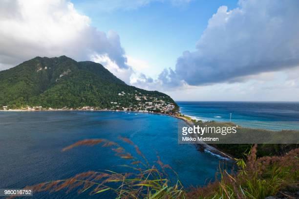 scotts head towering over caribbean sea shore, scotts head, dominica - dominica fotografías e imágenes de stock