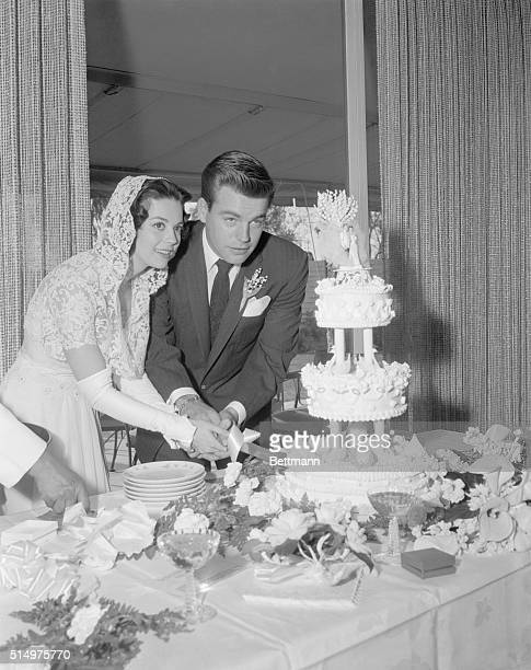 screen stars Natalie Wood and Robert Wagner cut their wedding cake at reception following simple wedding ceremony attended only by family and friends