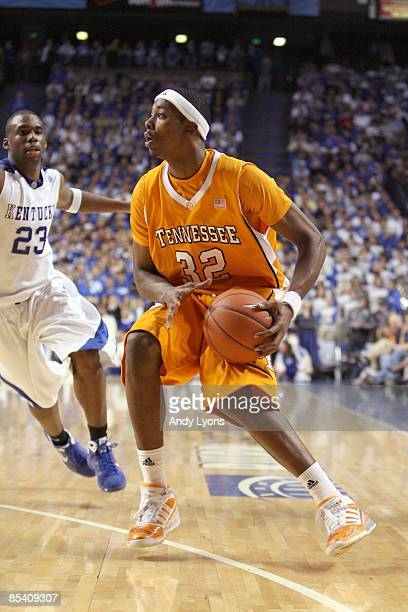 Scotty Hopson of the Tennessee Volunteers drives the ball against Jodie Meeks of the Kentucky Wildcats during the SEC game against at Rupp Arena on...