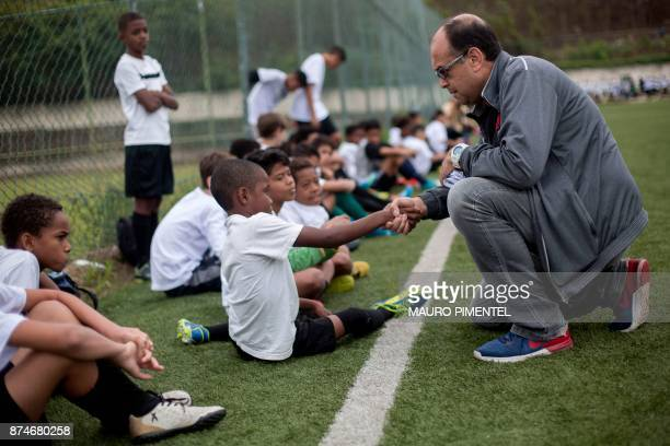 Scout Jorge Athayde speaks to a boy during a trial known as 'Peneira' in Portuguese in which youngsters play under the watch of scouts from one of...
