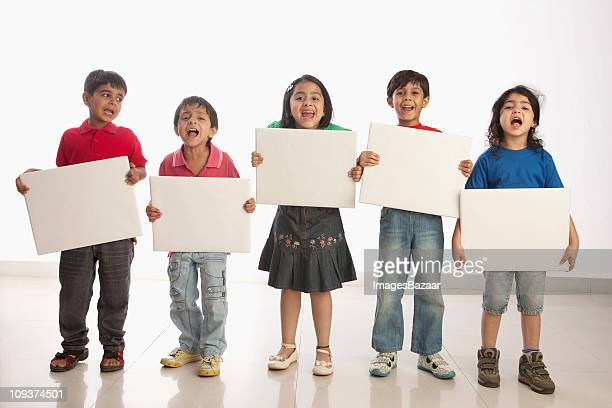 scouting girls (4-5, 6-7) and boys (4-5) holding white boards - placard stock pictures, royalty-free photos & images